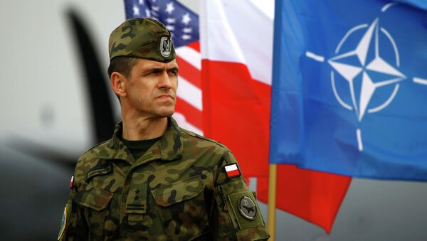 A Polish soldier stands near US and Poland's national flags and a NATO flag in Swidwin, northern west Poland, April 23, 2014 - Sputnik Türkiye