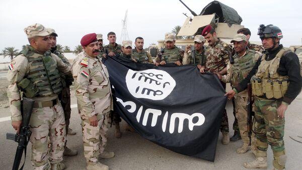 Irak askerleri, IŞİD'den geri aldıkları Ramadi'de bir binadan indirdikleri örgüt bayrağı ile poz verdi - Sputnik Türkiye