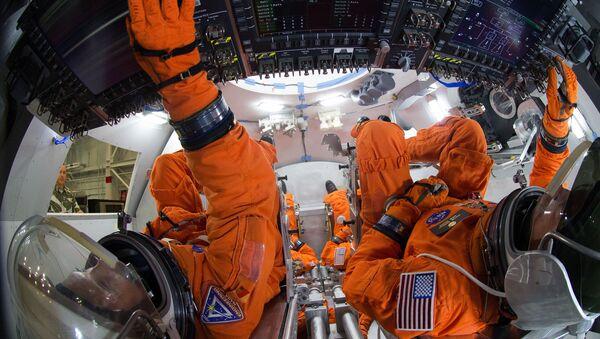 Uzay kıyafetleri içindeki mühendisler NASA'nın Orion uzay aracı içinde 4 mürettebat üyesinin nasıl bir düzen oluşturacaklarını Johnson Uzay Merkezi'nde bulunan modelde uygulamalı olarak gösteriyor. Orion, mürettebatlı ilk uçuşunu 2021 yılında gerçekleştirecek. 2030'lu yıllarda insanların Mars'a gönderilmesi bu uzay aracıyla planlanıyor. - Sputnik Türkiye