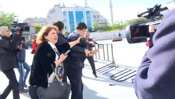 Can Dündar'ın eşi Dilek Dündar silahlı saldırı girişiminde bulunan kişinin yakından tutarak kaçmasını engellemeye çalıştı. - Sputnik Türkiye