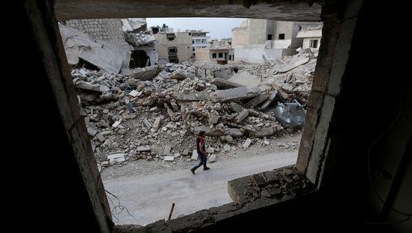 Suriye'nin İdlib kentinde bir adam, 'muhaliflerin' kontrolündeki bölgede yürüyor. - Sputnik Türkiye