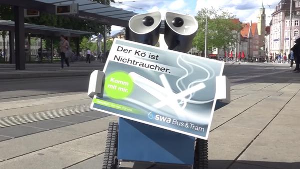 Almanya'da 2008 ABD yapımı Wall-E filmindeki aynı isimli çevreci robot, Alman vatandaşlarını kamusal alanlarda sigara içilmemesi konusunda uyarıyor. - Sputnik Türkiye