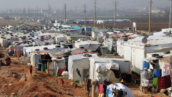 Syrian refugees walk at a refugee camp in Zahle in the Bekaa valley November 18, 2014 - Sputnik Türkiye