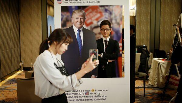 Güney Kore'nin başkenti Seul'deki bir otelde genç bir kadın Trump'ın fotoğrafı ile kendi resmini çekiyor. - Sputnik Türkiye