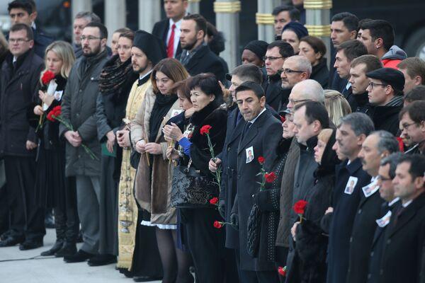Törende Karlov'un ailesi ve ona yakın olanların ellerinde kırmızı güller taşıdığı görüldü. - Sputnik Türkiye