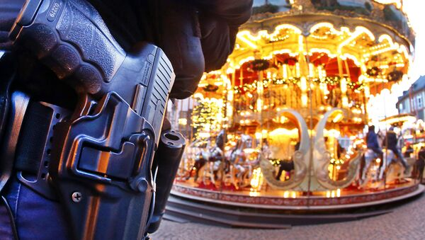 A German police officer stands next to a merry-go-round in the Christmas market in Frankfurt, Germany, Tuesday, Dec. 20, 2016 one day after a truck ran into a crowded Christmas market in Berlin killing several people - Sputnik Türkiye