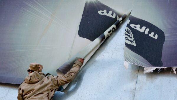 IŞİD'den geri alınan Musul'a giren Irak askerleri, örgütün bayrağının olduğu posterleri indirirken - Sputnik Türkiye