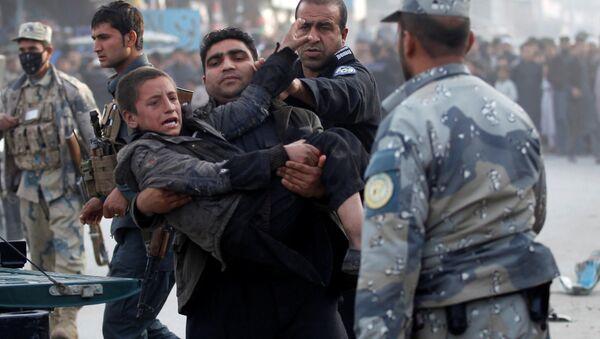 Afgan polisi Celalabad'daki bir bombalı saldırıda yaralanan çocuğu taşıyor - Sputnik Türkiye