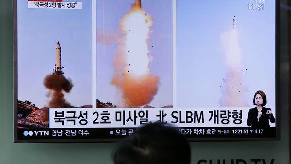 Güney Koreliler televizyondan Kuzey Kore'nin yaptığı balistik füze denemesi ile ilgili haberleri izliyor. - Sputnik Türkiye