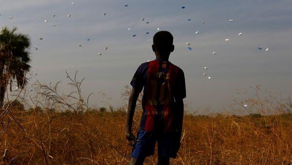 Güney Sudan'da BM Dünya Gıda Programı'nın havadan attığı gıda yardımlarını izleyen bir çocuk - Sputnik Türkiye