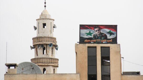 Hama'ya bağlı Suran kasabasında bir caminin yanında bulunan Suriye Devlet Başkanı Beşar Esad'ın fotoğrafının yer aldığı pano - Sputnik Türkiye