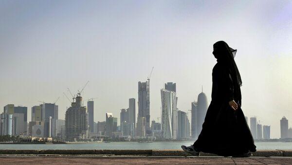A Qatari woman walks in front of the city skyline in Doha, Qatar. - Sputnik Türkiye