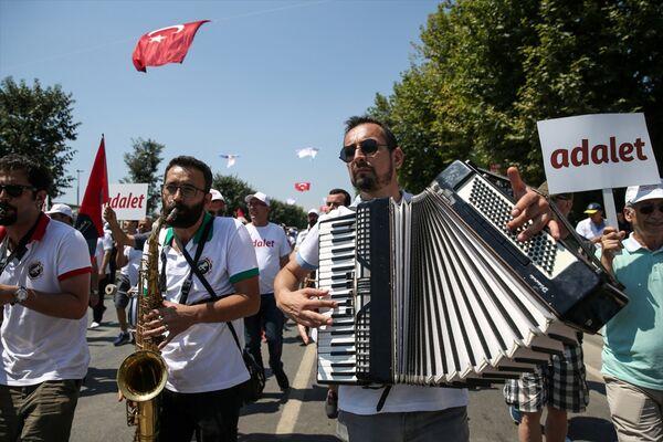 Ellerinde Atatürk posterleri, Türk bayrakları, 'adalet' yazılı flamalar bulunan katılımcılar, etkinlik sırasında 'Hak, hukuk, adalet' şeklinde slogan attı. Yürüyüş sırasında vatandaşların taşıdığı dev Türk bayrağı da alanda açıldı. - Sputnik Türkiye