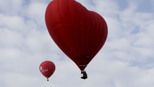 A heart-shaped hot air balloon (R) flies in the sky during the Love Cup 2016 event, ahead of Valentine's Day, in Jekabpils, Latvia, February 13, 2016 - Sputnik Türkiye