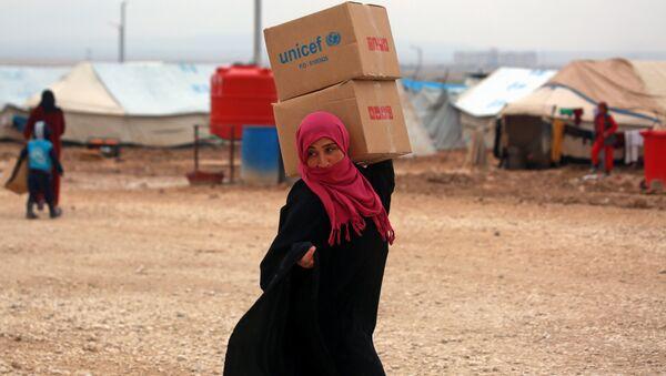 Suriyeli kadın sığınmacı Deyr Ez Zor'dan kaçmış Haseke'deki kampta UNICEF yardım kutularını taşıyor - Sputnik Türkiye