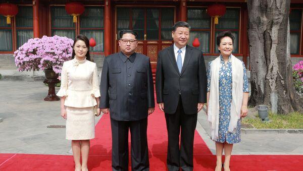 Çin'in resmi haber ajansı Şinhua'ya göre Kim, eşi Ri Sol-ju ile birlikte 25-28 Mart arası Çin lideri Şi Cinping'in daveti üzerine resmi bir ziyaret gerçekleştirdi. Kim, Ri, Şi ve Şi'nin eşi Peng Liyuan kameralara poz verdi. - Sputnik Türkiye