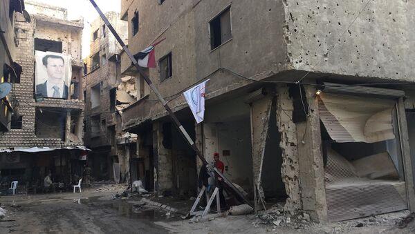Şam'ın güneyindeki Yermuk'ta Suriye Devlet Başkanı Beşar Esad'In fotoğrafının yer aldığı afiş - Sputnik Türkiye