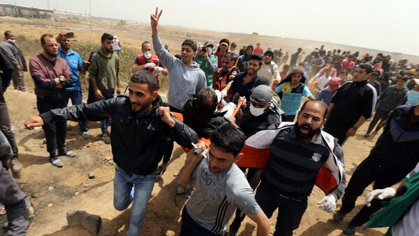 A wounded Palestinian is evacuated during clashes with Israeli troops at a protest demanding the right to return to their homeland, at the Israel-Gaza border, east of Gaza City, April 13, 2018 - Sputnik Türkiye