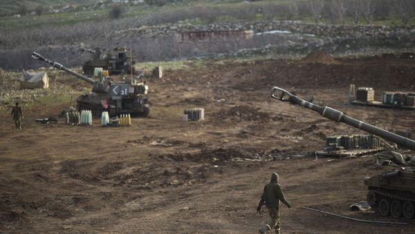 Israeli soldiers walk next to mobile artillery units in the Israeli-occupied Golan Heights near the border with Syria. (File) - Sputnik Türkiye