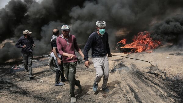 Palestinian protesters pull on a burning tire during clashes with Israeli forces on April 20, 2018, east of Khan Yunis, in the southern Gaza Strip during mass protests along the border of the Palestinian enclave, dubbed The Great March of Return, which has the backing of Gaza's Islamist rulers Hamas - Sputnik Türkiye