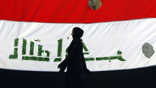 An Iraqi woman walks her national flag during a celebration marking the the departure of US troops from Iraq in Baghdad's Adhamiyah neighbourhood. File photo - Sputnik Türkiye
