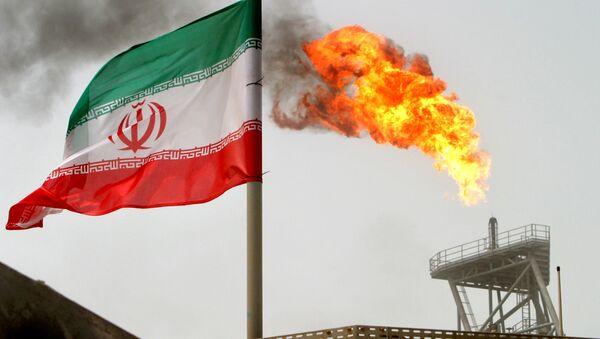 A gas flare on an oil production platform in the Soroush oil fields is seen alongside an Iranian flag in the Persian Gulf, Iran, July 25, 2005 - Sputnik Türkiye