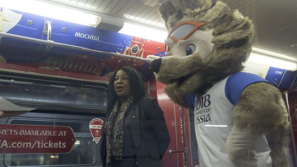 Fatma Samoura, FIFA Secretary General, left, speaks to the media with a mascot of the 2018 World Cup, the wolf named Zabivaka, seen at right, in the metro train branded for the 2018 World Cup during a ceremony in Moscow, Russia, on Tuesday, Nov. 28, 2017 - Sputnik Türkiye