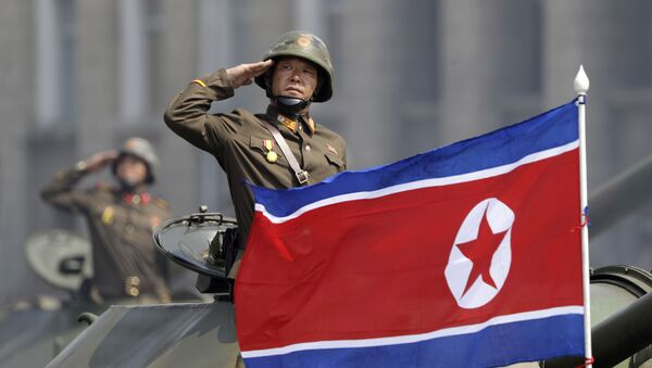 In this Saturday, April 15, 2017, file photo, a North Korean national flag flutters as soldiers in tanks salute to North Korean leader Kim Jong Un during a military parade in Pyongyang, North Korea to celebrate the 105th birth anniversary of Kim Il Sung, the country's late founder and grandfather of the current ruler - Sputnik Türkiye