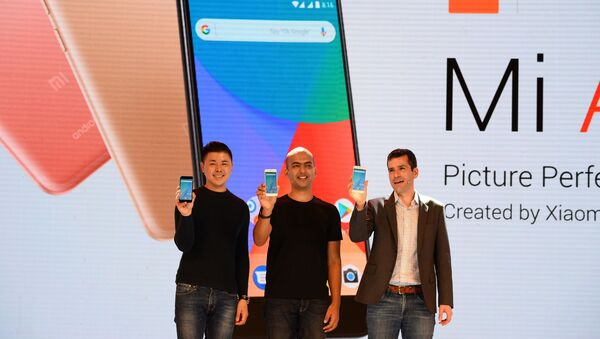 (L-R) Donovan Sung, director of product management and marketing at Xiaomi Global, Manu Jain, managing director of Xiaomi India, and global director of Android Partner Programs Jon Gold hold the newly launched Xiaomi Mi A1 smartphone at a function in New Delhi on September 5, 2017 - Sputnik Türkiye