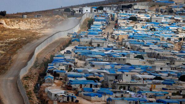 Suriye'nin İdlib vilayetinin Atameh kasabasını Türkiye sınırından bir duvar ayırıyor. - Sputnik Türkiye