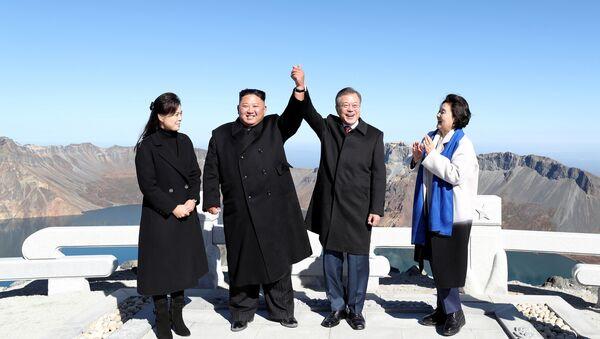 Pyongyang'da Sunan Uluslararası Havalimanı'ndan eşlerinin de yanlarında olduğu kendi özel jetleriyle Samjiyon Havaalanı'na inen Moon ve Kim, kutsal kabul edilen volkanik Paekdu Dağı'nın zirvesi Çanggun-bong'da el ele tutuşarak samimi görüntüler verdi. Dörtlü, dağın ünlü krateri Çonji etrafında da gezindi. - Sputnik Türkiye