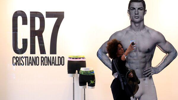 Bu sezon Real Madrid'den Juventus'a transfer olan Cristiano Ronaldo'nun çamaşır reklamının bulunduğu Milano'daki pano önünde bir kadın selfie çekiyor. - Sputnik Türkiye