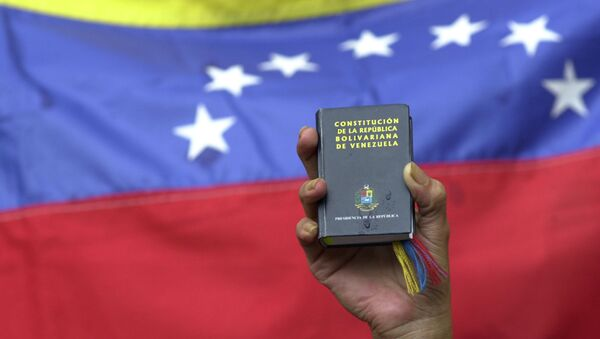 A demonstrator holds up a miniature copy of Venezuela's constitution in front of the nation's flag at a government rally in Caracas, Venezuela, Tuesday, April 13, 2004. - Sputnik Türkiye