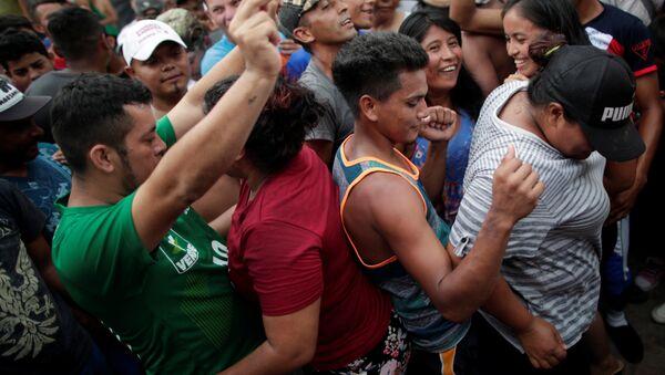 Orta Amerika ülkelerinden ABD'ye doğru harekete geçen binlerce kişilik göçmen kafilesi, 24 Ekim'de Meksika'nın Mapastepec kentinde dans ederken - Sputnik Türkiye