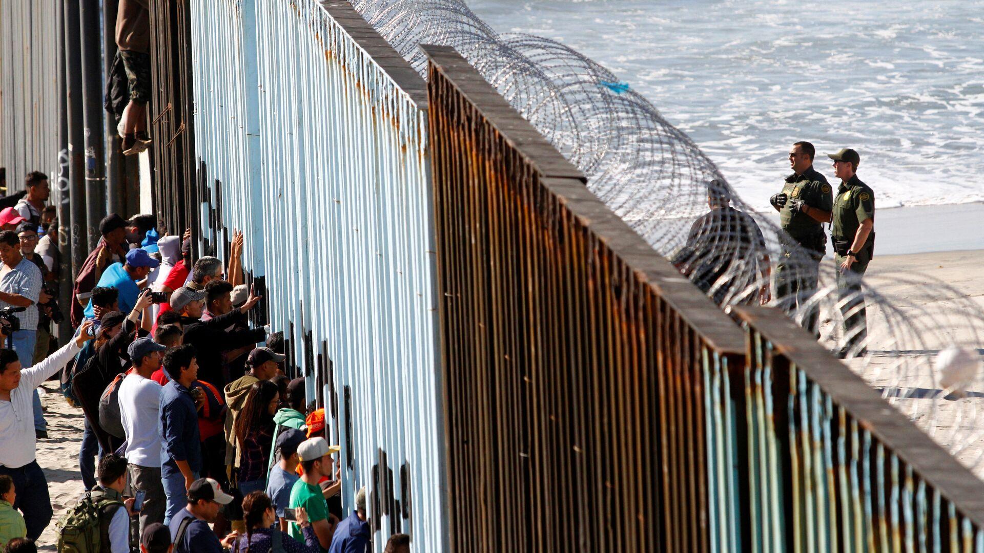 Orta Amerikalı göçmen kervanından 800-1000 kişilik bir grup, Meksika'nın ABD sınırındaki Tijuana'ya ulaştı. Göçmenler, kentte ABD ile sınırı belirleyen duvarı adeta kuşatmaya aldı. - Sputnik Türkiye, 1920, 21.09.2021
