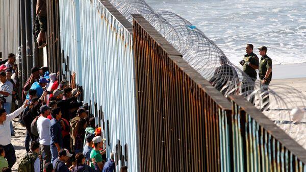 Orta Amerikalı göçmen kervanından 800-1000 kişilik bir grup, Meksika'nın ABD sınırındaki Tijuana'ya ulaştı. Göçmenler, kentte ABD ile sınırı belirleyen duvarı adeta kuşatmaya aldı. - Sputnik Türkiye