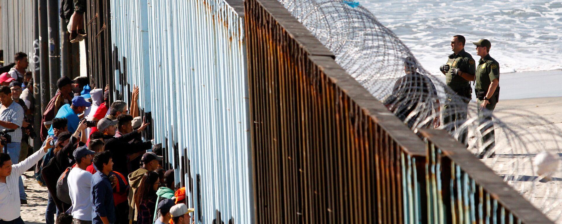 Orta Amerikalı göçmen kervanından 800-1000 kişilik bir grup, Meksika'nın ABD sınırındaki Tijuana'ya ulaştı. Göçmenler, kentte ABD ile sınırı belirleyen duvarı adeta kuşatmaya aldı. - Sputnik Türkiye, 1920, 05.08.2021