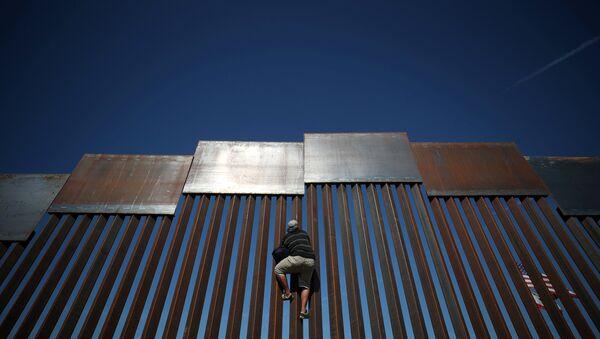 Meksika-ABD sınırındaki çitlere tırmanan bir göçmen - Sputnik Türkiye