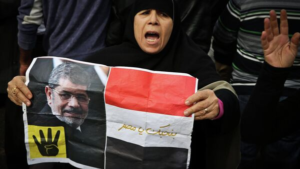 Mısır'da devrik Müslüman Kardeşler iktidarının hapisteki lideri Mursi'nin posteriyle bir kadın - Sputnik Türkiye
