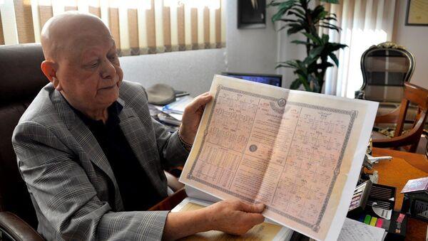 Babasına ait sandıktan, dedesinin babasına ait olduğu düşünülen 1917 yılına ait tahvil çıktığını söyleyen Antalya'da 79 yaşındaki turizmci Akay Okudur - Sputnik Türkiye