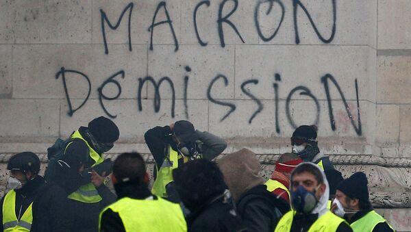 Sarı Yelekler hareketi, talepleri arasında yer alan Macron'un istifasını Paris'teki Zafer Takı'na da yazdı. - Sputnik Türkiye