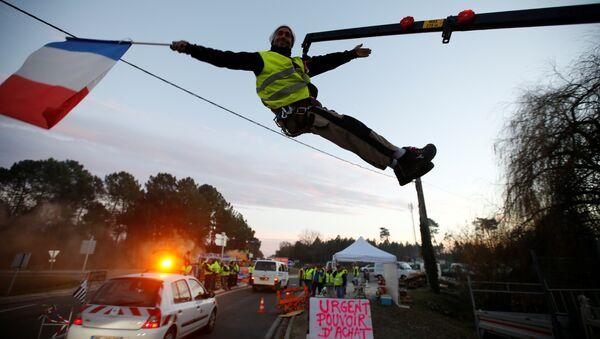 Sarı Yelekler Fransa'nın Cissac-Medoc bölgesinde bir kavşağı işgal edip kontrol noktası kurarken, içlerinden biri vinçten sarkarak elindeki Fransa bayrağıyla  araçları selamladı. - Sputnik Türkiye