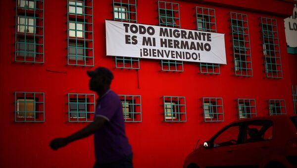 Şili'de Haitili bir göçmen ve Tüm göçmenler kardeşimizdir, Hoşgeldiniz yazılı bir pankart - Sputnik Türkiye