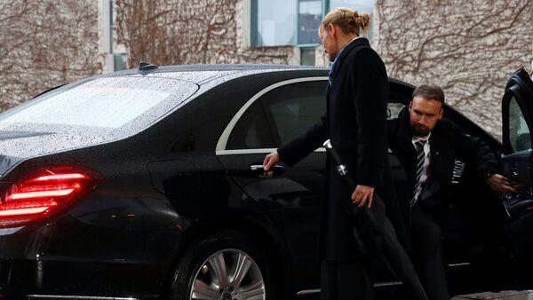 Merkel'in şaşkın bakışları arasında biri kadın biri erkek iki yardımcı kapıyı açabilmek için kolu çekiştirip düğmeleri kurcaladı. Kısa bir uğraşının ardından kapı açıldı ve May dışarı çıktı. - Sputnik Türkiye