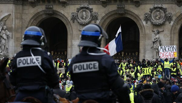 15 Aralık'ta Paris'teki Opera binası önünde atlı polislerin kuşattığı Sarı Yelekler'den biri, Fransa Cumhurbaşkanı Emmanuel Macron'a hitaben Defol git yazılı dövizi havaya kaldırmış halde görülüyor. - Sputnik Türkiye
