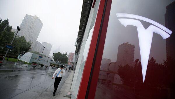 A man walks near a logo of Tesla outside its China headquarters at China Central Mall in Beijing, China July 11, 2018 - Sputnik Türkiye