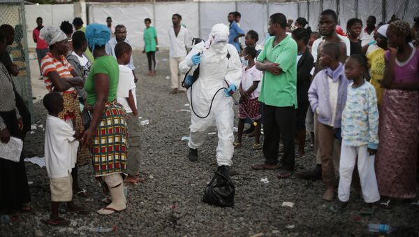 In this file photo daetd Tuesday, Sept. 30, 2014, a medical worker sprays people being discharged from the Island Clinic Ebola treatment center in Monrovia, Liberia - Sputnik Türkiye