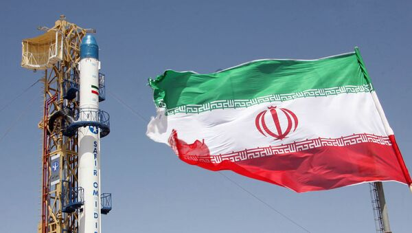 Iranian flag fluttering in front of Iran's Safir Omid rocket, which is capable of carrying a satellite into orbit, before it's launch in a space station at an undisclosed location in the Islamic republic - Sputnik Türkiye