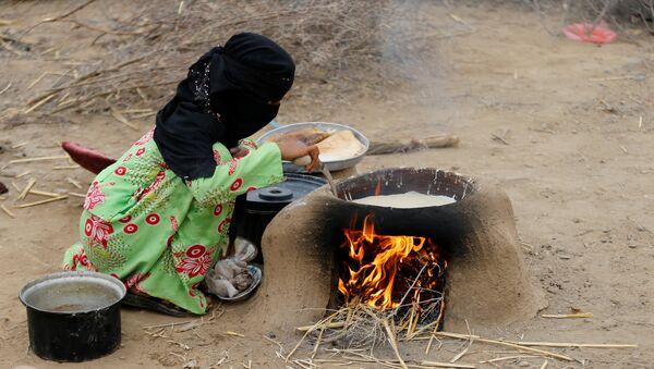 Yemen'in kuzeybatısındaki Hacca eyaletinin Abs kenti yakınında savaşta evsiz, yersiz kalanların oluşturduğu kampta bir kadın elde olanlarla yemek pişirmeye çalışıyor.  - Sputnik Türkiye