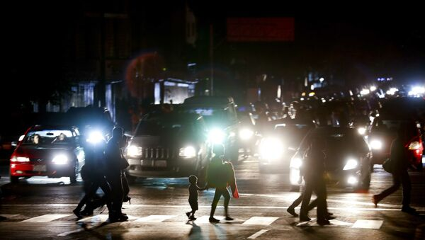 Residents cross a street in the dark after a power outage in Caracas, Venezuela, Thursday, March 7, 2019. A power outage left much of Venezuela in the dark early Thursday evening in what appeared to be one of the largest blackouts yet in a country where power failures have become increasingly common. Crowds of commuters in capital city Caracas were walking home after metro service ground to a halt and traffic snarled as cars struggled to navigate intersections where stoplights were out. - Sputnik Türkiye
